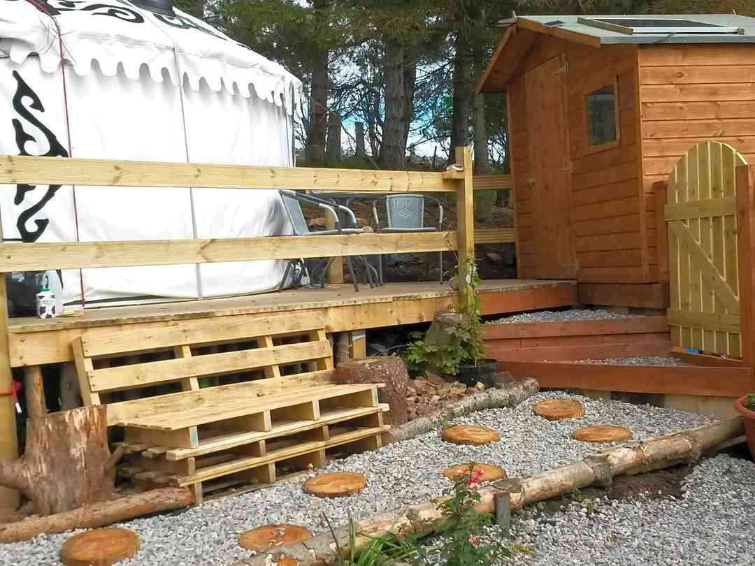 The Tall Pines Yurt: Outside yurt showing pebbled path leading to yurt decking, toilet/shower