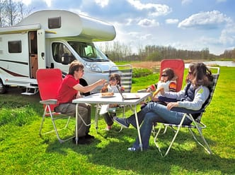 A happy family relax outside their motorhome