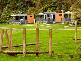 Glamping pods and nearby children's play area at Alderstead Heath Experience Freedom Glamping Site