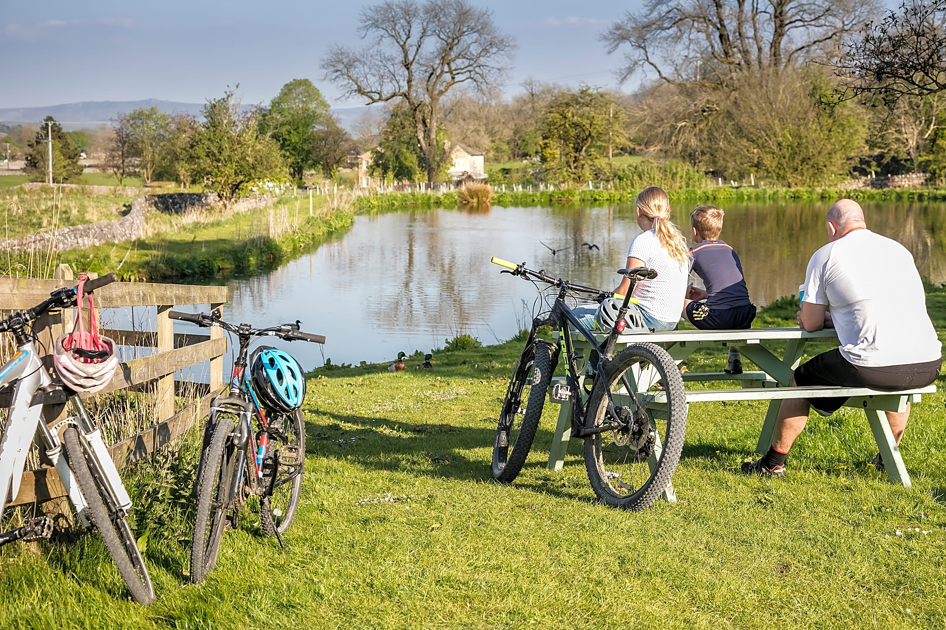Family cycling by the pond