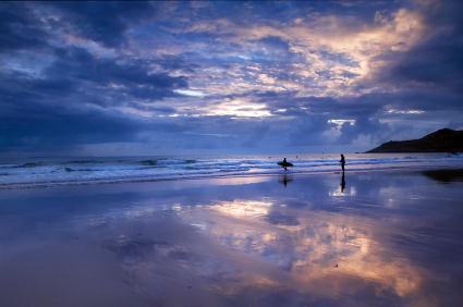 Surfers at sunset on Woolacombe beach, Devon, England